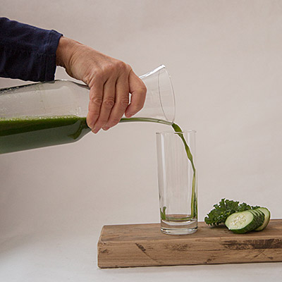 pouring a glass of green giant cold pressed raw juice